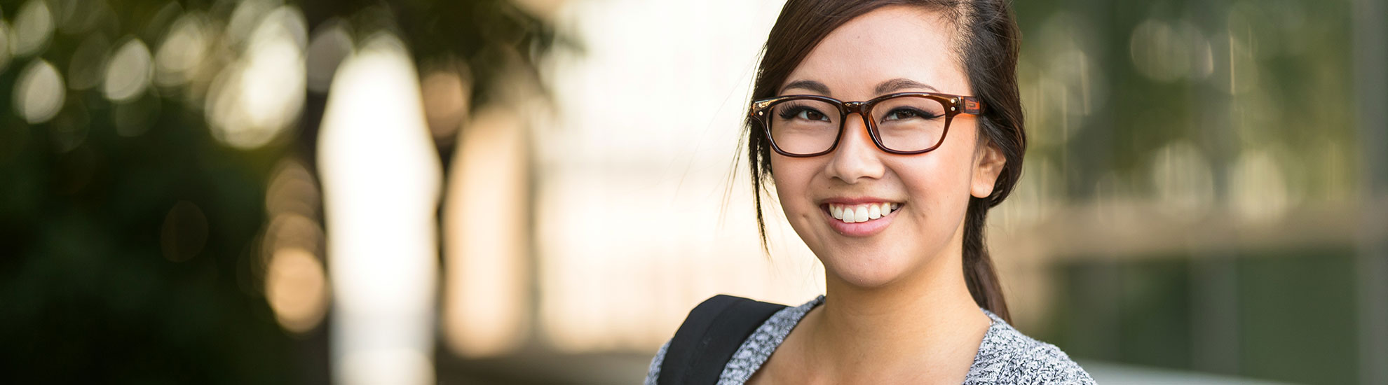 Young woman smiling outsides wearing glasses
